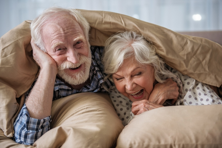 Cheerful Old Married Couple Lying In Bed Under Blanket. Woman Is